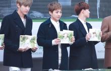 Kris, Xiumin, Suho Holding Respective Photos