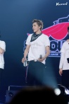 Kris in a white EXO SMTOWN Week logo T-shirt with a black hankerchief tied around his neck
