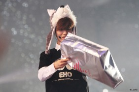 Luhan in a wolf hat looking into a gift bag