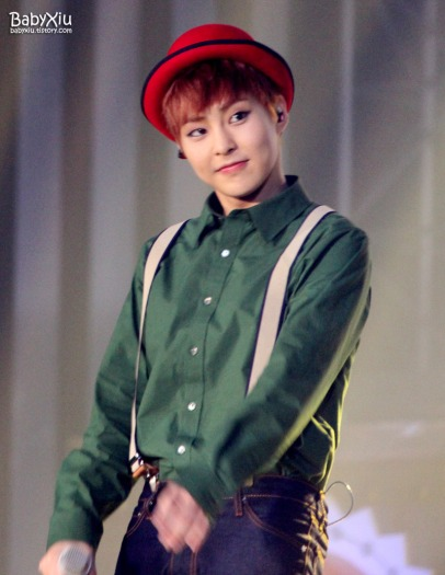 Xiumin in a green shirt with a red hat and suspenders